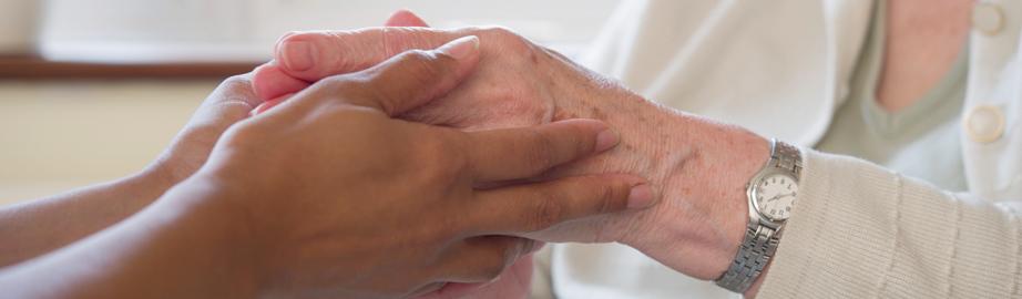 Carer holding elderly woman's hands