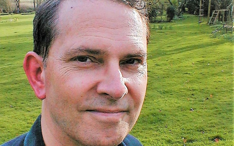 close up portrait of Jonathan Yonge. He's wearing a blue shirt and is in a garden with a green lawn in the background.