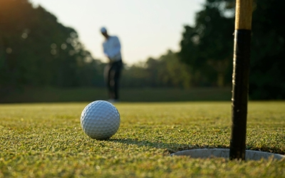 close up of a golf ball, on the green, inches away from the hole. The golfer can be seen, out of focus, in the distance.
