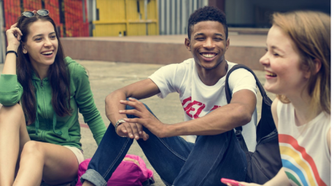 Three teenagers sit outside chatting and laughing together.