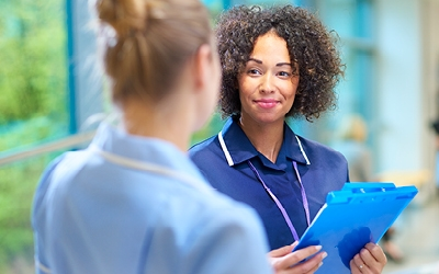 Nurses talking and holding clipboard