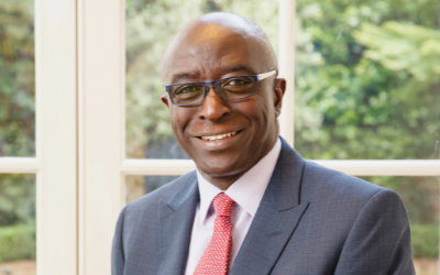 portrait of Professor Kwame Akyeampong. He is sitting in front of a window, facing the camera and smiling. He is wearing a red tie and glasses.