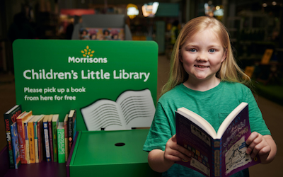 A young (junior aged) girl in a green top looks at the camera, holding open a book. She is standing beside a stand advertising the Morrison's Children's Little Library.