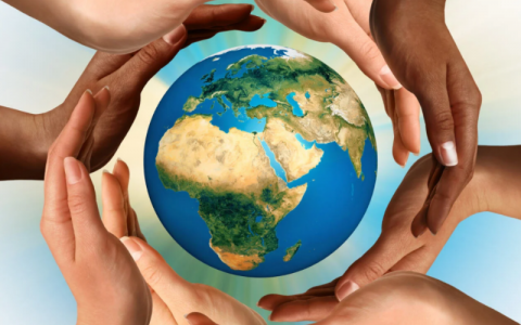 Eight hands of different ethnicities surround a 3D graphic image of the world in an overlapping circle. The globe is pictured with Africa, Asia and Europe in view.