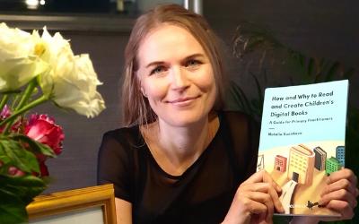 Photograph of Professor Natalia Kucirkova holding up her winning book.