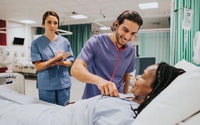 A nurse takes a patient's observations while a trainee nurse makes notes in the background