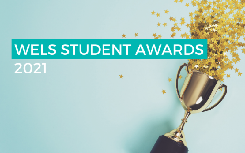 """Photograph of a trophy on it's side, spilling star confetti on to a clean, blue background. The text """"WELS STUDENT AWARDS 2021"""" is overlaid on top of the image."""