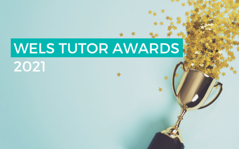 """Photograph of a trophy on its side, spilling star confetti on to a clean, blue background. The text """"WELS TUTOR AWARDS 2021"""" is overlaid on top of the image."""